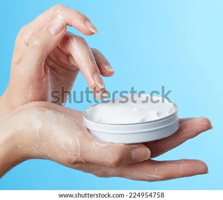 Woman's hands with moisturizer cream on blue background - stock photo