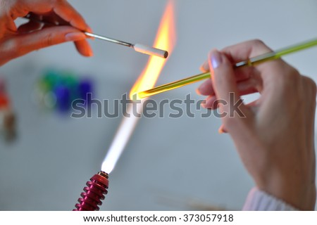 woman's hands with tools for glass melting, the time of production of glass ornaments - stock photo