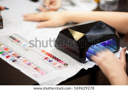 Woman's hands with UV lamps at nail studio - stock photo