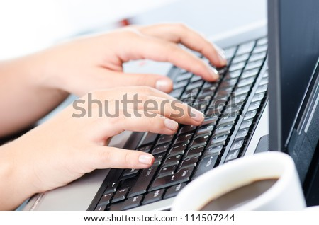 Woman's hands working on notebook keyboard at the desk