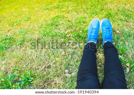 Woman's leg lying on grass with colorful shoe and afternoon light