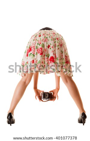 Woman's legs and hand, unusual back view of girl taking picture using vintage camera isolated on white background - stock photo