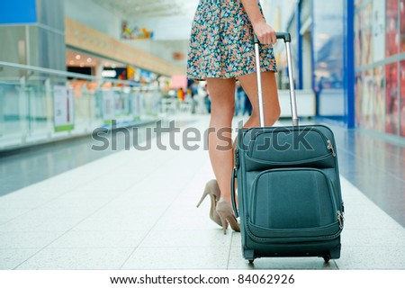Woman's legs and travel suitcase at international airport tax free shopping zone - stock photo