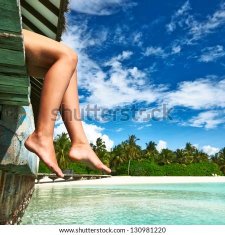 Woman's legs at beach jetty - stock photo