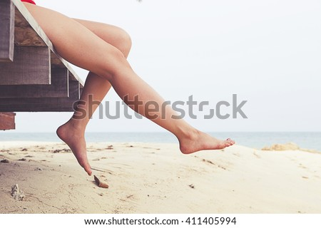 Woman's legs at beach jetty - stock photo
