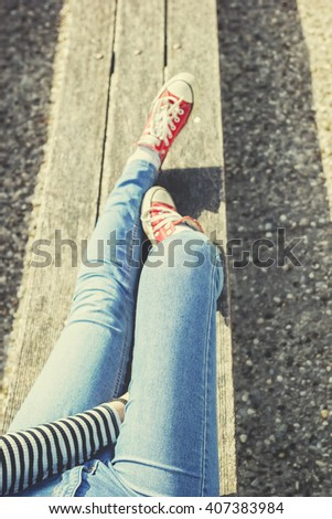 Woman's legs in a blue jeans and red canvas sneakers sitting on a bench - stock photo
