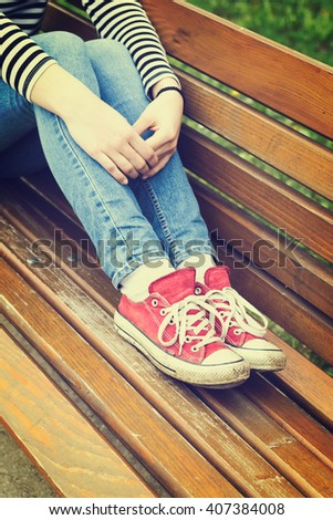 Woman's legs in a blue jeans and red canvas sneakers sitting on a bench. Retro styled photo. - stock photo