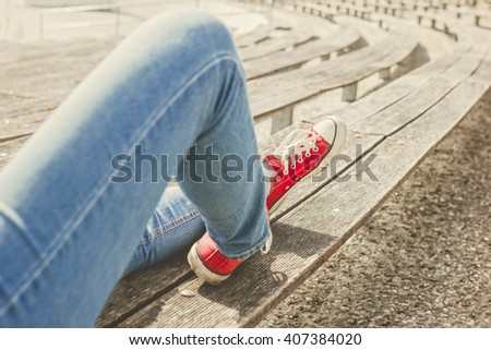Woman's legs in a blue jeans and red canvas sneakers sitting on a bench. Rows of benches in a background. - stock photo