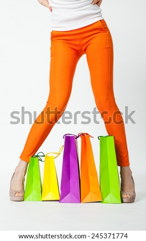 Woman's legs in orange pants and multicolored shopping bags, shopping concept - stock photo