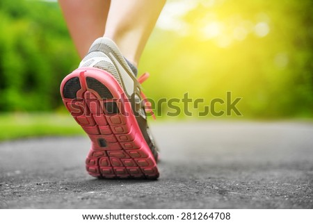 Woman's legs in shoes on runner jogging in the park at sunset. - stock photo