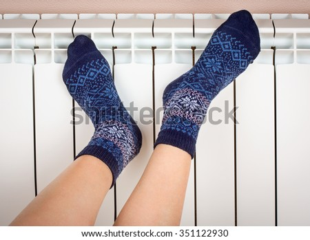 Woman's legs in socks on white radiator background - stock photo