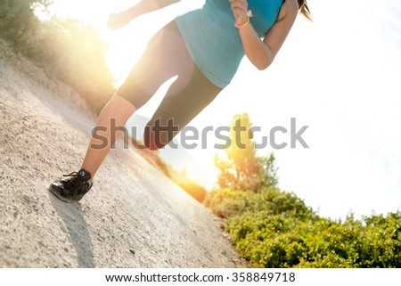 Woman's legs running outdoors at sunset hour