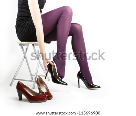 Woman's Legs Trying on Shoes with a White Studio Background - stock photo