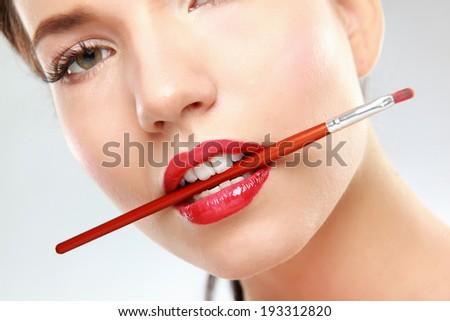 Woman's lips holding make up brush - stock photo