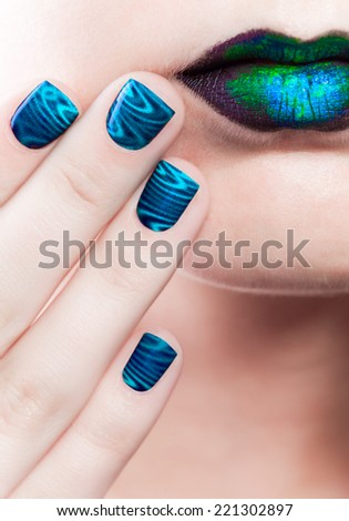 Woman's lips with beautiful multicolor holographic Minx nails and bright colorful make-up