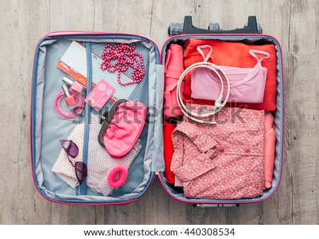 Woman's open bag on a desktop with clothing and accessories, she is packing and getting ready to leave, travel and vacations concept - stock photo