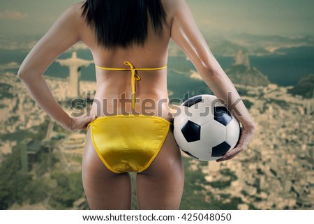 Woman's Sexy Backside Holding a Soccer Ball and looking at  - stock photo