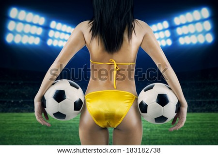 Woman's Sexy Backside Holding a Soccer Ball. Shoot at soccer stadium - stock photo