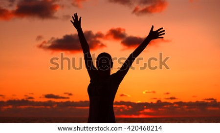 Woman's silhouette in sunset light, happy girl with raised up hands standing on the beach and enjoying warm summer evening, victory concept  - stock photo