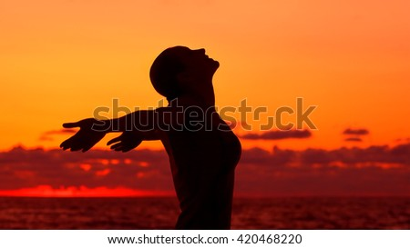Woman's silhouette on sunset background, happy girl with raised hands standing on the beach and looking up in the sky, enjoying summer vacation - stock photo
