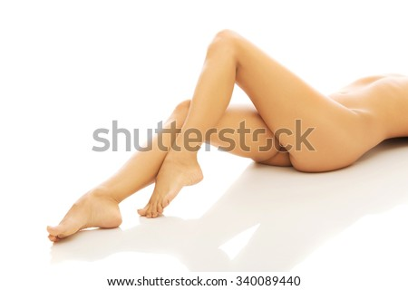Woman's slim nude legs, buttock and slim belly. - stock photo