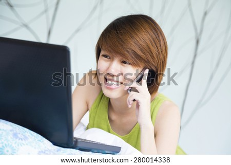 Woman's smiling while she's talking on the phone and playing computer - stock photo