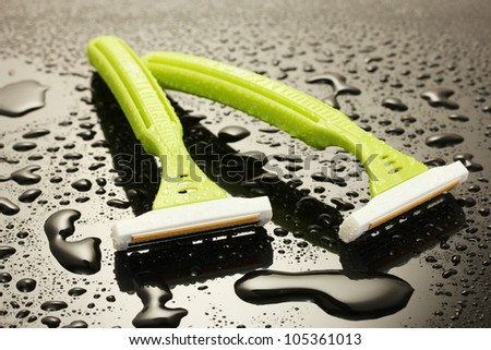woman safety shavers and flowers with drops on grey backgroud