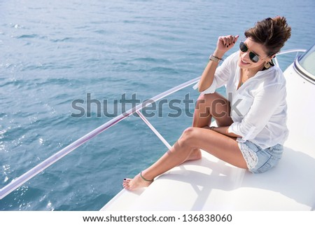 Woman sailing in a yacht on her summer holidays - stock photo