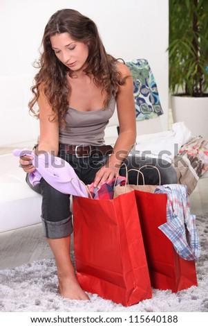 Woman sat looking through shopping bags - stock photo