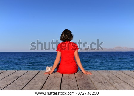 Woman sat on jetty at Majorca, Balearic Islands, Spain.