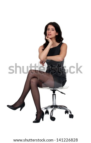Woman sat on office chair - stock photo