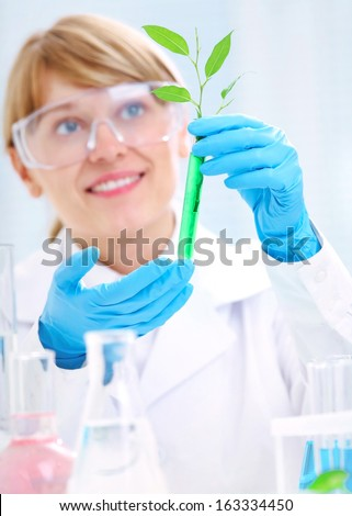 Woman scientist holding a test tube with plant. Ecology - stock photo