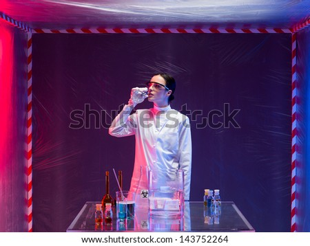 woman scientist in a containment tent, wearing a white lab coat, next to a table with chemicals, smelling a substance from a bottle - stock photo