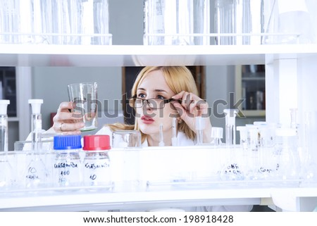 Woman scientist with laboratory flask - stock photo