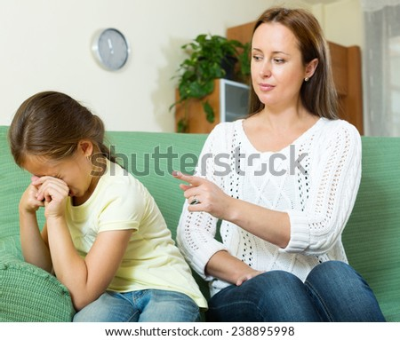 Woman scolding crying child at home interior. Focus on girl - stock photo