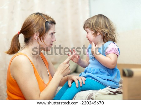 Woman scolds crying child at home interior. - stock photo