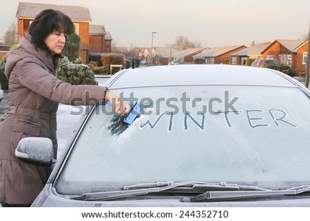 Woman scraping ice from a car windscreen, starting to remove the word winter that is written in the ice. - stock photo