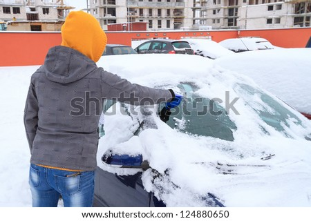 Woman scraping ice from the car window in winter time - stock photo