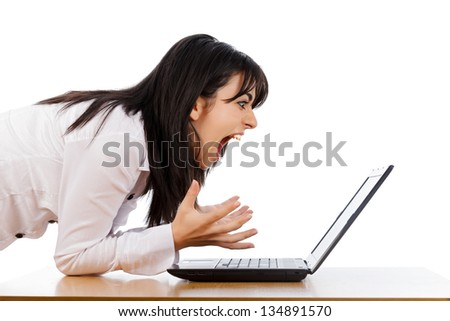 Woman screaming nervously at the laptop isolated on white. - stock photo