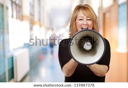 Woman screaming on a megaphone, indoor - stock photo