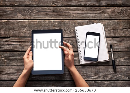Woman scroll down screen of digital tablet. And smartphone is on notepad. Clipping paths included.