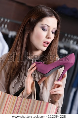Woman scrutinizes elegant fuchsia shoes at the store - stock photo
