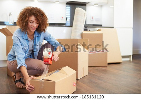 Woman Sealing Boxes Ready For House Move - stock photo
