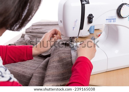 Woman seamstress thread inserts in the sewing machine. Close-up. - stock photo