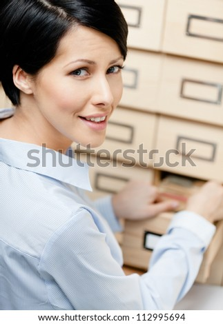 Woman searches something in card catalog composed of set of wood boxes at the library. Knowledge
