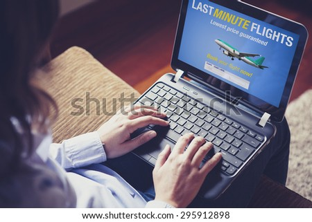Woman searching for a last minute flight on the internet. She is typing on the laptop keyboard. - stock photo