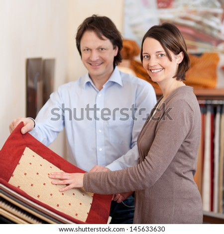 Woman searching for carpet samples standing looking at a sample book accompanied by a smiling young husband or salesman - stock photo