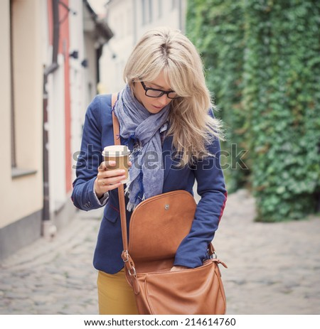 Woman searching for stuff in her handbag. - stock photo