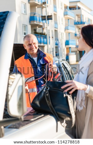 Woman searching her purse mechanic fixing car breakdown problem insurance - stock photo