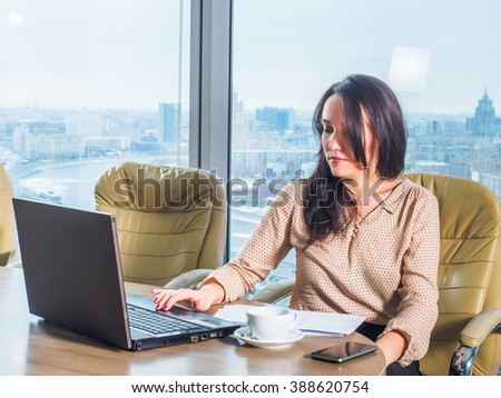 Woman secretary with dark hair sitting in the office with panoramic windows on the computer - stock photo